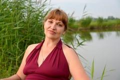 成熟妇女的画象以湖为背景的 库存照片