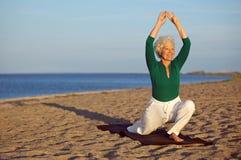 成熟妇女舒展在海滩的-瑜伽 免版税图库摄影