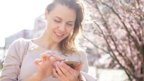成熟妇女藏品智能手机在她手和微笑上 木兰在城市街道,春天画象上开花 股票录像