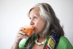 成熟妇女饮用的红萝卜汁 图库摄影