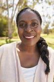 成熟妇女首肩画象在公园 免版税库存照片