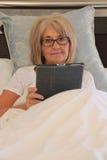 成熟妇女读书片剂在床上。 免版税图库摄影