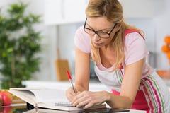 成熟妇女读书菜谱在寻找食谱的厨房里 免版税图库摄影
