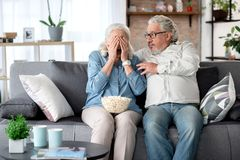 成熟已婚夫妇有趣的观察的害怕的电视节目 图库摄影