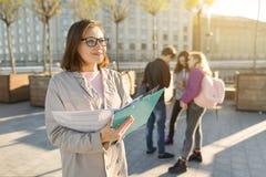 成熟微笑的女老师画象玻璃的与剪贴板,与一个小组的outdor少年学生 免版税库存图片