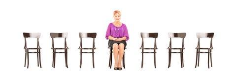 成熟微笑的妇女坐木椅子和等待的j 库存照片