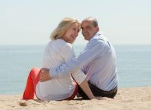 成熟恋人坐海滩 免版税库存图片