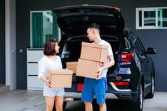 成熟愉快的亚洲人在新的家与从车厢的夫妇运载的纸板箱结婚 库存图片