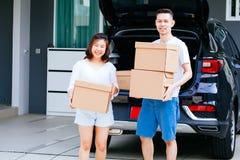 成熟愉快的亚洲人在新的家与从车厢的夫妇运载的纸板箱结婚 免版税库存图片
