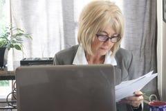 成熟成人女商人与膝上型计算机和纸一起使用。 免版税库存图片