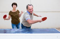 成熟打乒乓球的男人和妇女 免版税库存照片