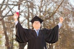 成熟打手势幸福的毕业生户外 图库摄影