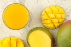 成熟新鲜的芒果果子和切片和芒果汁在一块玻璃在轻的背景 r r 库存图片