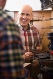 成熟普通的在针车床的工作员缝合的皮靴  免版税图库摄影