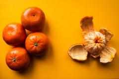 成熟普通话和被剥皮的普通话在橙色bacground 免版税图库摄影