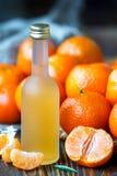 成熟普通话或蜜桔酒在一个小瓶,选择聚焦新鲜的汁液  免版税图库摄影