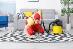 成熟有吸尘器的人hoovering的地毯 免版税图库摄影