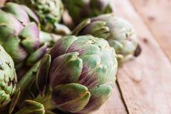 成熟有机朝鲜蓟,绿色和紫色颜色,驱散在板条木桌上被窗口,健康地中海饮食 免版税库存照片