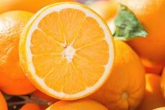 成熟有机桔子堆在农夫市场上 一果子用可看见的纹理明亮的充满活力的颜色切成了两半 Vitamis Superfood 图库摄影