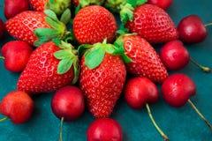 成熟有机草莓,以花,蓝色背景,被称呼的创造性的图象,特写镜头的形式安排的光滑的甜樱桃 免版税库存图片
