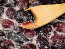 成熟李子在糖浆被烹调并且与一把木匙子混合 免版税图库摄影