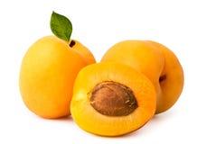 成熟杏子和一个一半与一根骨头在白色,被隔绝 免版税库存图片