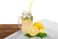 从成熟柠檬、绿色薄菏新鲜的叶子和矿泉水的夏天圆滑的人在白色背景隔绝的一个巨大的金属螺盖玻璃瓶 图库摄影