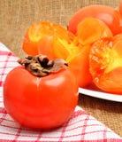 成熟柿子在白色板材和napking结果实,袋装backg 库存照片