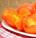 成熟柿子在白色板材和napking结果实,袋装backgr 免版税图库摄影