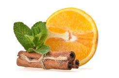 成熟桔子、薄荷叶和肉桂条的新水多的构成 免版税图库摄影