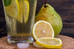 成熟梨柠檬水用柠檬和薄菏在黑暗的背景 库存图片