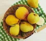 成熟梨生物在白色木背景的板材维生素土气收获营养 图库摄影