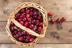 成熟樱桃一个大篮子  可口和甜莓果 木背景,文本的自由空间 减速火箭的样式 复制空间 免版税库存照片