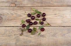 成熟樱桃和樱桃叶子在一张木桌上 免版税库存照片