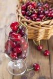 成熟樱桃和疏散莓果一个大篮子在桌上和在玻璃 木背景,文本的自由空间 减速火箭 免版税库存图片