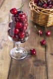 成熟樱桃和疏散莓果一个大篮子在桌上和在玻璃 木背景,文本的自由空间 减速火箭 免版税图库摄影