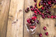 成熟樱桃和疏散莓果一个大篮子在桌上和在玻璃 木背景,文本的自由空间 减速火箭 图库摄影