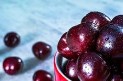成熟樱桃在老牌搪瓷铁瓶子结果实, 免版税库存照片