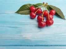 成熟樱桃莓果健康甜鲜美维生素可口在蓝色木背景,夏天框架 免版税库存图片