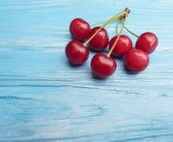 成熟樱桃莓果健康鲜美维生素可口在蓝色木背景,夏天框架 库存图片
