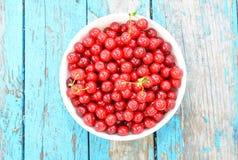 成熟樱桃 在蓝色木背景的樱桃 在颜色碗的新鲜的樱桃 免版税库存照片