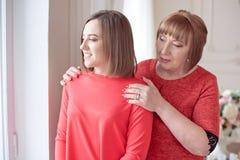 成熟母亲拥抱站立在她后的女儿 免版税库存图片