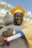 成熟毕业生拥抱的父亲 免版税库存图片
