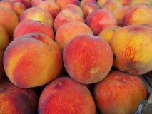 成熟水多的桃子被堆积在市场摊位 库存照片