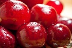 成熟水多的樱桃射击了与汁液下落的特写镜头莓果表面上的  免版税库存图片