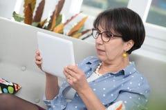成熟深色的妇女坐沙发使用数字式片剂 库存照片