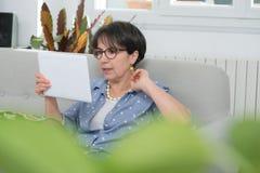 成熟深色的妇女坐沙发使用数字式片剂 库存图片