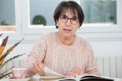 成熟深色的妇女读书杂志 库存照片