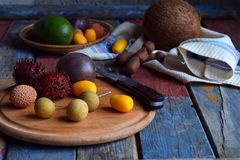 成熟热带水果的混合用西番莲果,金桔, lychee,红毛丹,罗望子树,鲕梨,椰子,在木后面的龙眼睛 图库摄影