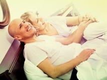 成熟爱恋的夫妇lounging在床上在醒拥抱以后 免版税库存照片